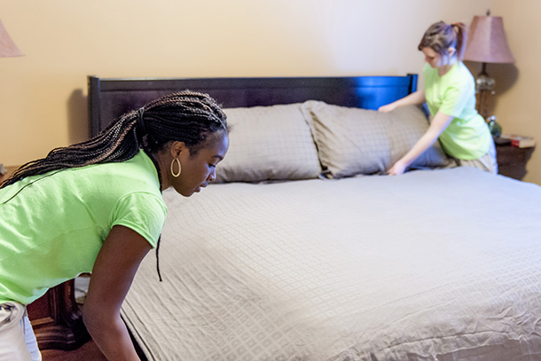 Merry Maids Making Up a Bed