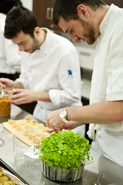Kitchen staff carefully placing garnish