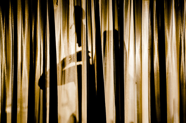 Artistic image of stand up base player through stage curtains