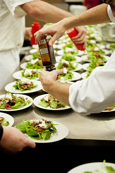 Chef and staff add dressig to rows of salads
