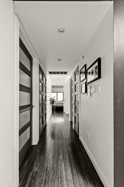 View of hallway with wood floors and doors