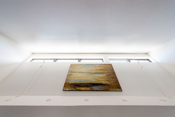 Looking up at artwork and row of skylights