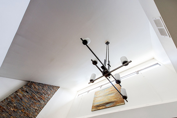 Looking up at light fixture, artwork and multi color brick wall