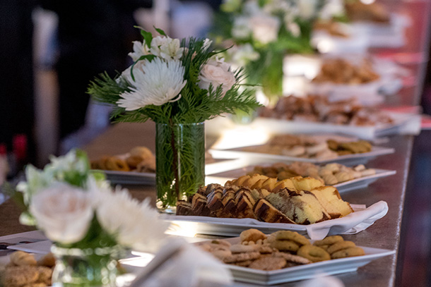 Platters of treats and flowers line a table