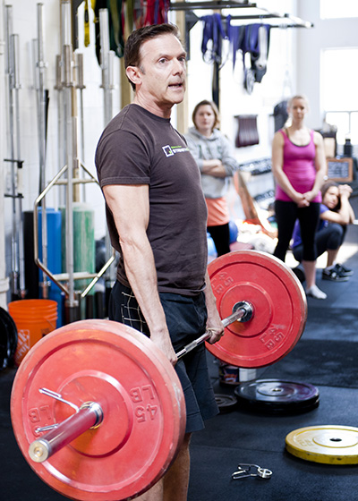 Greg Carver Founder and Certified Trainer lifts weights