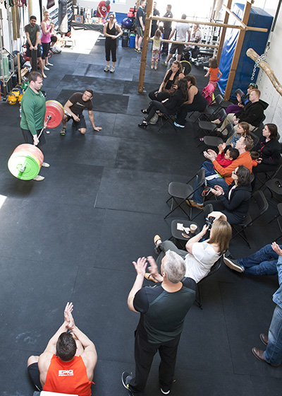 Participant powerlifts while group watches