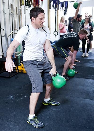 Participants lift kettlebells
