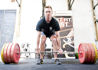 Participant prepares to powerlift, hands are on the weight bar