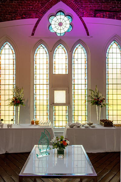 Tables with flowers and awards sit in front of the church windows