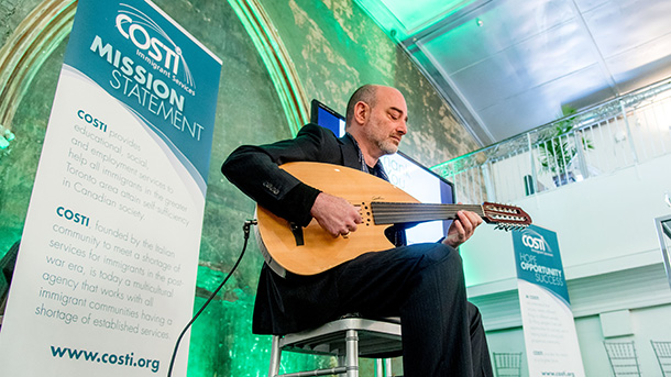 Musician performs for the guests on stage as they enter