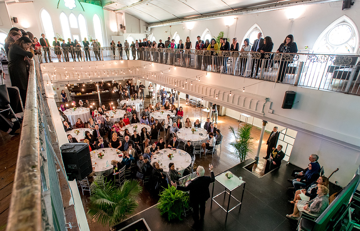 View of the event underway, balcony and main floor are full of guests