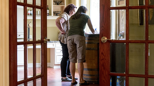 2 team members writing on top of wine barrel