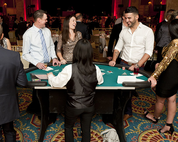 A dealer deals cards to players at the black jack table