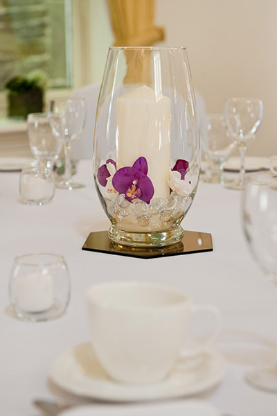 Wedding decor, orchids in a vase decorate the middle of a table