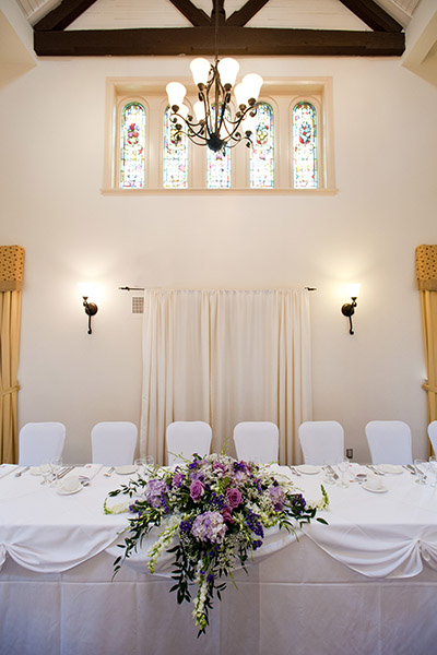 Wedding reception head table with beautiful flowers and table setting