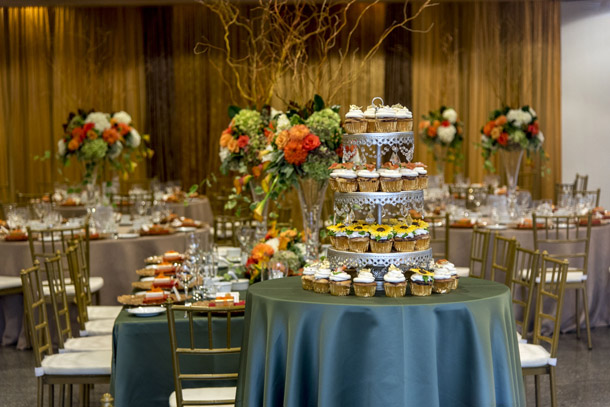 View of table settings, cake display and gold curtain decor